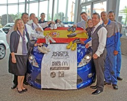 Staff at a Dagenham Motors dealership collecting football boots during the World Cup for charity Boots for Africa.